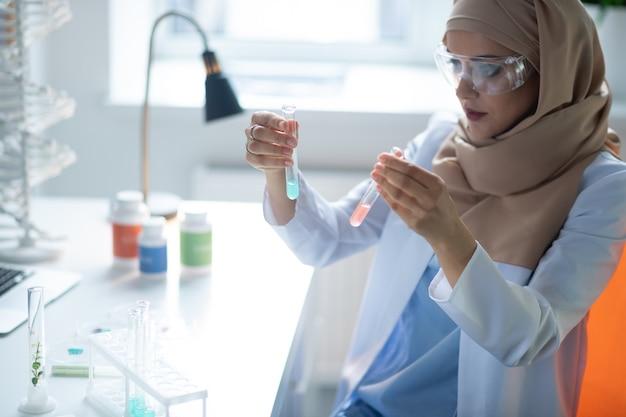 Compare os agentes químicos. química feminina usando hijab e óculos comparando dois agentes químicos