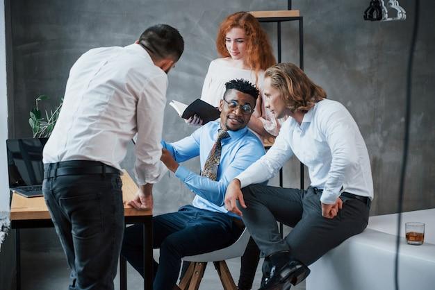 Compartilhando algumas idéias. grupo de trabalhadores de escritório multirracial em roupas formais falando sobre tarefas e planos