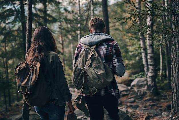 Compartilhando amor com a natureza. vista traseira de um jovem casal caminhando juntos na floresta enquanto aproveita a viagem