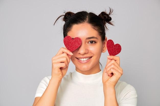 Compartilhando amor e namorados. mulher jovem e atraente morena com uma camiseta branca moda casual segurando dois corações brilhantes sobre os olhos e um lindo sorriso