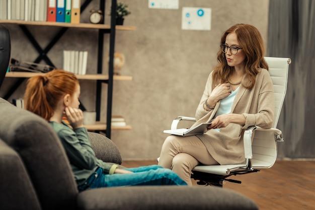 Compartilhando experiência. mulher agradável e agradável apontando para si mesma enquanto compartilha sua experiência com seu jovem paciente