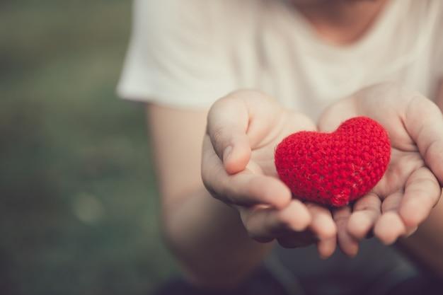 Compartilhando o amor e coração cor vermelha na mão de mulheres no tom de cor vintage de dia dos namorados
