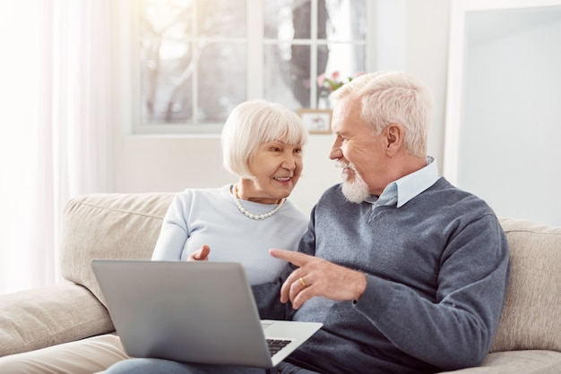 Compartilhando opiniões. marido e mulher sênior alegres, sentados no sofá da sala de estar e discutindo um artigo juntos, depois de lê-lo online