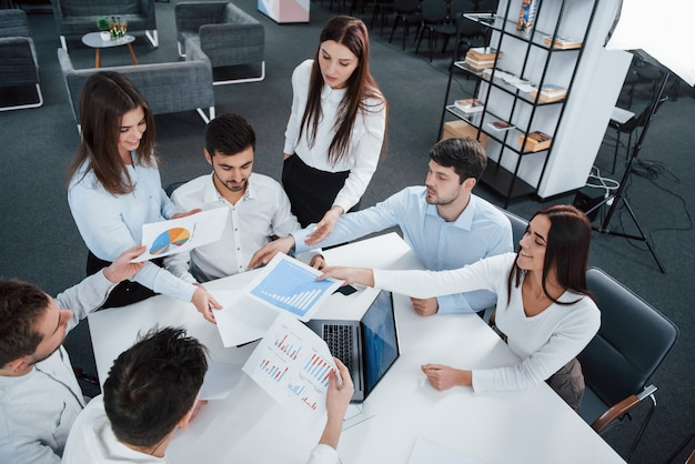 Compartilhando papéis com gráficos. vista superior dos trabalhadores de escritório em roupas clássicas, sentado perto da mesa usando o laptop e documentos