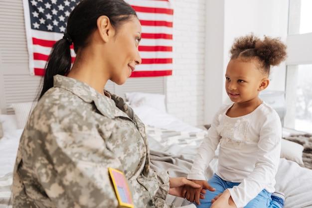 Compartilhando segredos. mãe muito jovem e enérgica e seu filho conversando muito sentados em uma cama depois de passarem muito tempo longe um do outro
