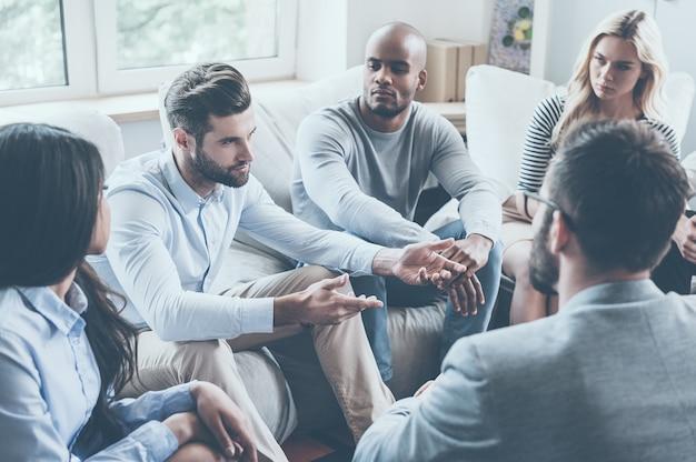 Compartilhando seus problemas com o grupo. grupo de jovens sentados em círculo enquanto um homem diz algo e gesticula