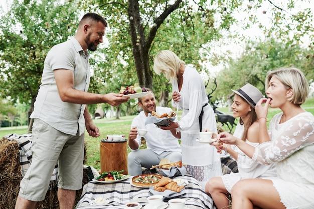 Compartilhando sobremesas. grupo de amigos adultos descansam e conversam no quintal do restaurante na hora do jantar.