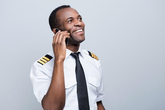 Compartilhar notícias após o pouso. vista lateral do feliz piloto africano de uniforme segurando o telefone celular