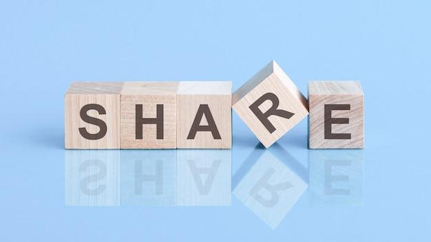 Compartilhe a placa feita de blocos em uma mesa com uma superfície reflexiva, fundo azul