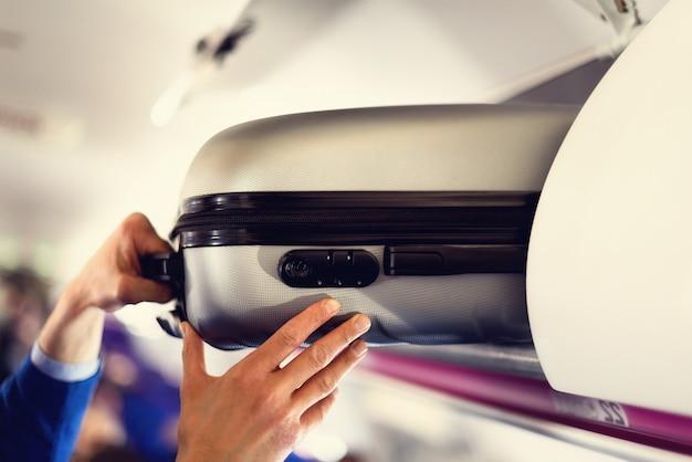 Compartimento de bagagem de mão com malas no avião.