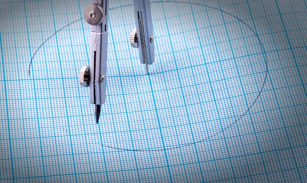 Compassescompasses e um círculo pintado em papel milimetrado azul