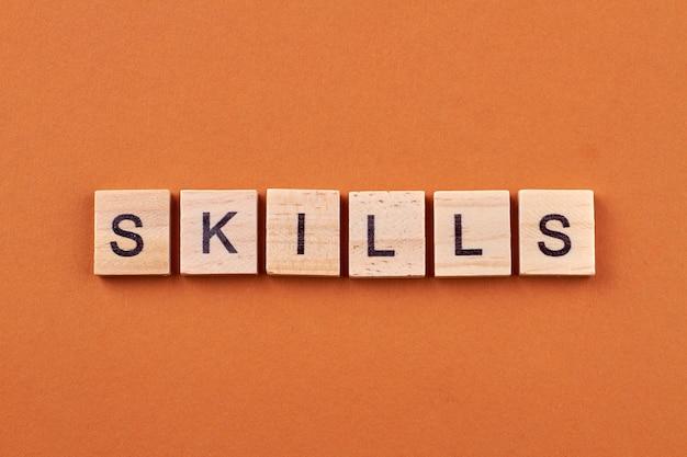 Competências e conceito de desenvolvimento. texto de habilidades em cubos de madeira isolados em fundo laranja.