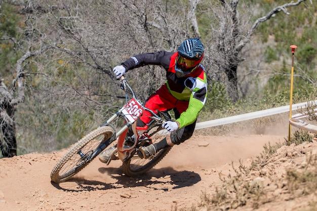 Competição de downhill, biker monta rápido no campo.