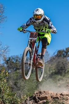 Competição de downhill, motociclista salta rápido no campo.