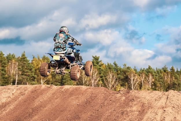 Competição de motocross, homem salta com moto-quatro