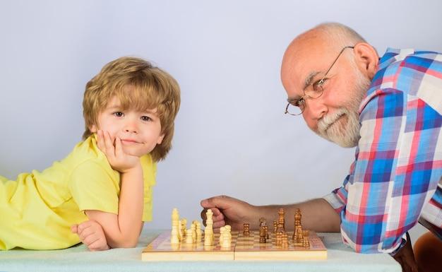 Competição de xadrez infantil e de tabuleiro, garotinho jogando xadrez com o vovô.