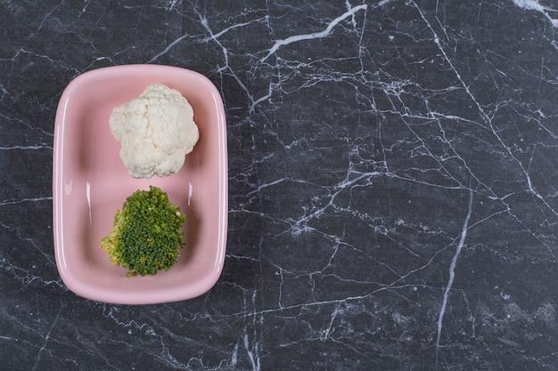 Complete a vista de couve-flor fresca e brócolis em uma tigela rosa.