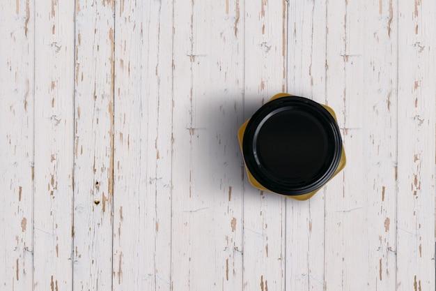 Complete o frasco de geléia de laranja de vista isolado no fundo branco de madeira. adequado para o seu projeto de design.