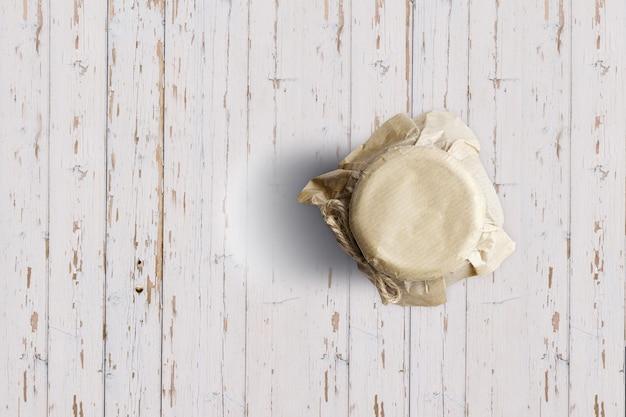 Complete o frasco de geléia de mirtilo de vista isolado no fundo branco de madeira. adequado para o seu projeto de design.