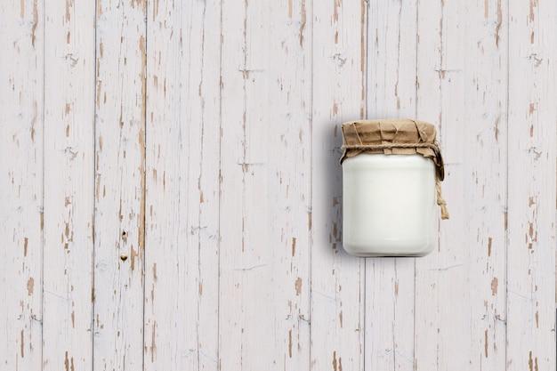 Complete o frasco de iogurte de vista isolado no fundo branco de madeira. adequado para o seu projeto de design.