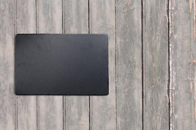 Complete o quadro de exibição preto na mesa vintage de madeira escura. adicionado espaço de cópia para texto, adequado para seu fundo de conceito de comida ou bebida.