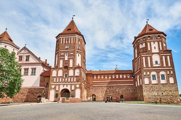 Complexo do castelo mir em dia de verão com céu azul nublado. marco turístico na bielo-rússia, monumento cultural