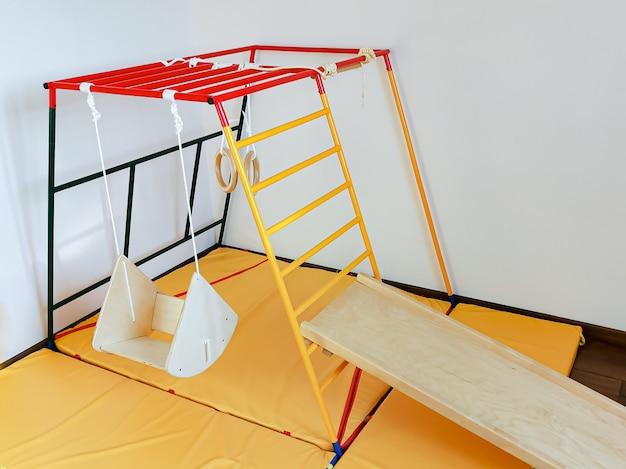 Complexo esportivo infantil para a criança no apartamento balanço de madeira, estrutura de escalada, escorregador e argolas de ginástica.