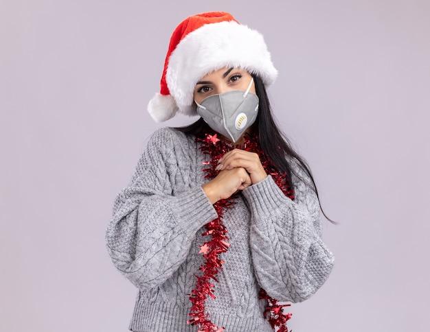 Complicada jovem caucasiana usando chapéu de natal e guirlanda de ouropel em volta do pescoço com máscara protetora, mantendo as mãos juntas isoladas na parede branca com espaço de cópia