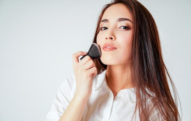 Compo o kabuki da escova na mão da jovem mulher asiática de sorriso com cabelo longo escuro no branco