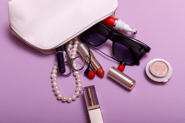 Compõem a bolsa com cosméticos isolados no fundo rosa