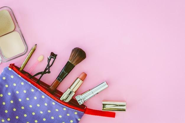 Compõem o saco com cosméticos em fundo rosa