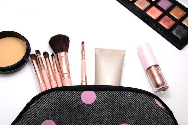 Compõem o saco de cosméticos conjunto decorativo, ferramentas de maquiagem em fundo branco.