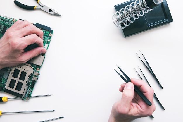 Componentes de computador de solda plana lay. vista superior nas mãos do reparador consertando a peça quebrada na placa-mãe do laptop. conserto de eletrônicos, construção, conceito de negócio