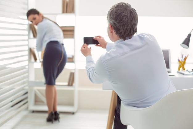 Comportamento inapropriado. homem simpático, desagradável e bonito usando seu smartphone e tirando fotos de seu colega enquanto está sentado à mesa