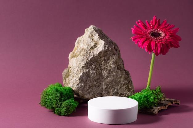 Composição abstrata com pódio branco, pedra, musgo e flor