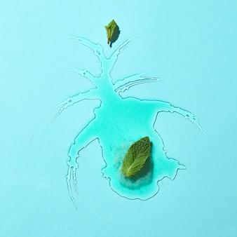 Composição abstrata de sorvete derretido em um fundo de vidro azul com folhas de hortelã, limites claros e reflexão. vista do topo