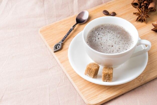 Composição acolhedor com uma xícara de café em uma bandeja com açúcar em um cobertor de café pastel plana leigos, vista superior.