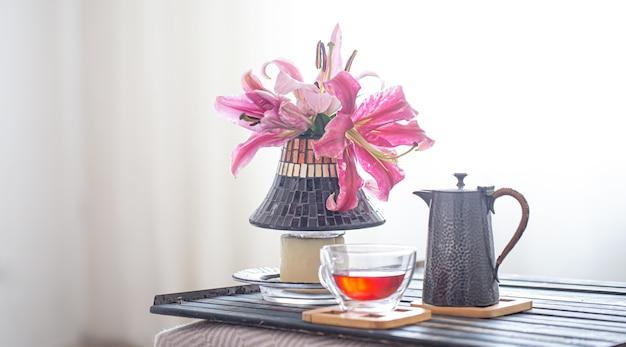Composição aconchegante com bandeja de madeira com bule e xícara de chá e lindas flores de lírio.