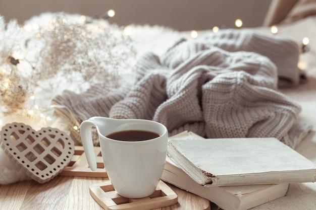 Composição aconchegante com café em pires e detalhes de decoração para casa.