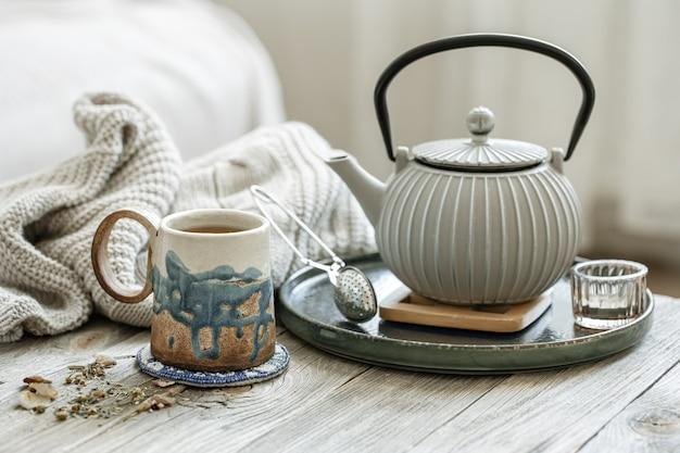 Composição aconchegante com uma xícara de cerâmica, um bule e um elemento de malha em um fundo desfocado.