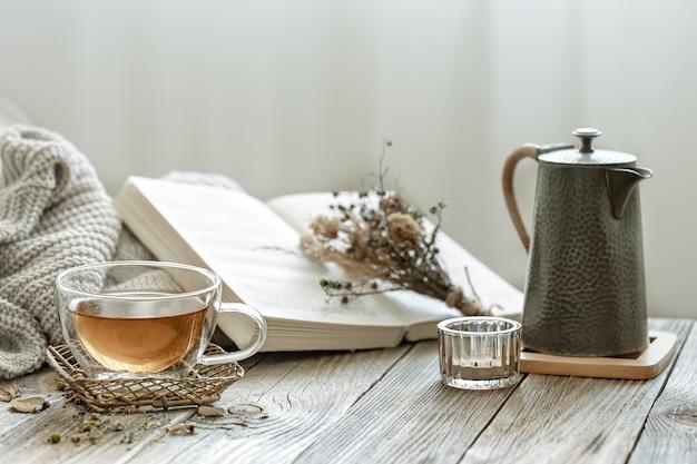 Composição aconchegante com uma xícara de chá e um livro no interior da sala sobre um fundo desfocado.