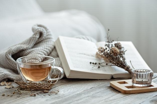 Composição aconchegante com uma xícara de chá e um livro no interior da sala