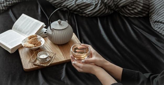 Composição aconchegante com uma xícara de chá nas mãos femininas, biscoitos e um livro na cama.