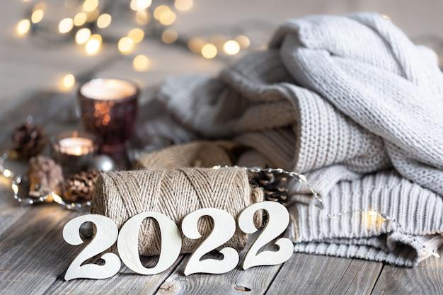 Composição aconchegante de ano novo com números decorativos 2022, elementos de malha e luzes de bokeh.