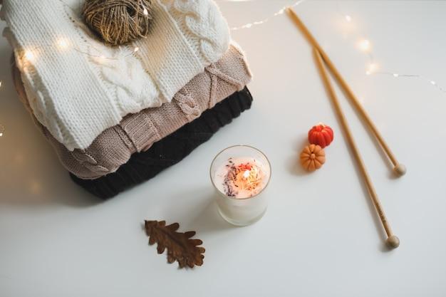 Composição aconchegante de inverno e outono com roupas de malha de agulhas e vista de cima de uma vela