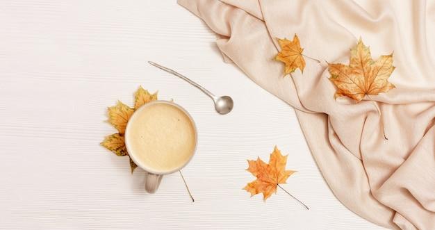 Composição aconchegante de outono com folhas secas de bordo e xícara de café