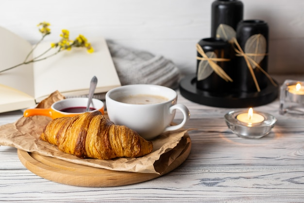 Composição aconchegante hygge com croissant caseiro fresco e café na mesa de madeira branca com velas, livros e malhas
