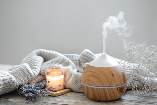 Composição aromática com difusor de óleo aromático moderno sobre superfície de madeira com elemento de malha, vela e lavanda.