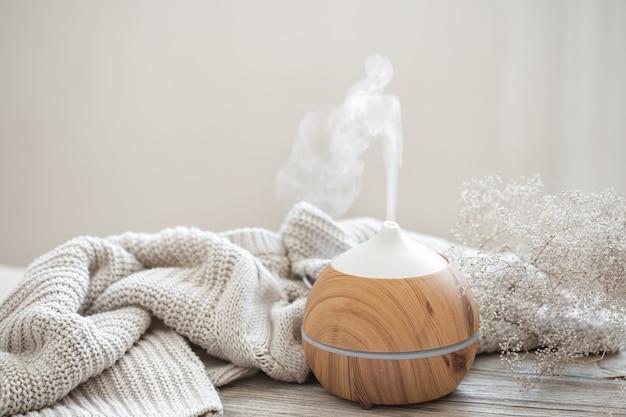 Composição aromática com difusor de óleos aromáticos moderno sobre superfície de madeira com elemento de malha e ramo de flores secas.