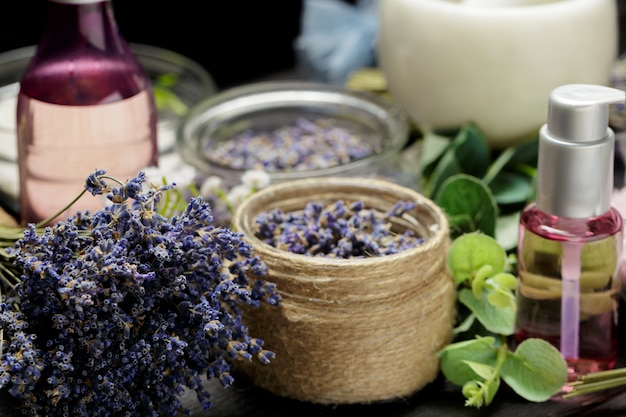 Composição aromática de lavanda, ervas, cosméticos e sal em cima de uma mesa escura